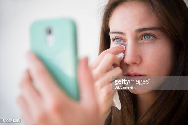 Native American woman with cell phone wiping away tears