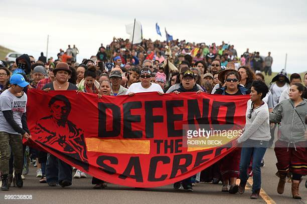 Native Americans march to the site of a sacred burial ground that was disturbed by bulldozers building the Dakota Access Pipeline near the encampment...