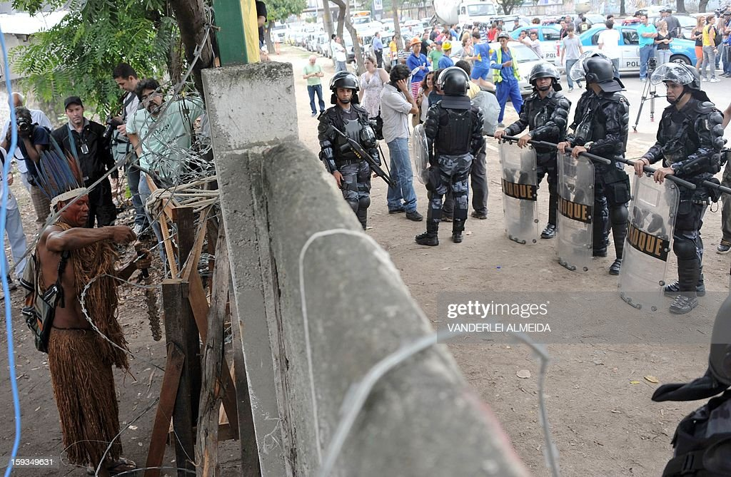 A native blocks a gate as riot police officers stand guard at the entrance of the old indigenous museum --aka Aldea Maracana-- next to Maracana stadium in Rio de Janeiro on January 12, 2013. Indians have been occupying the place since 2006 as a protest against Rio de Janeiro's governmet decision to throw them out and pull down the building to construct 10,500 parking lots for the upcoming Brazil 2014 FIFA World Cup.