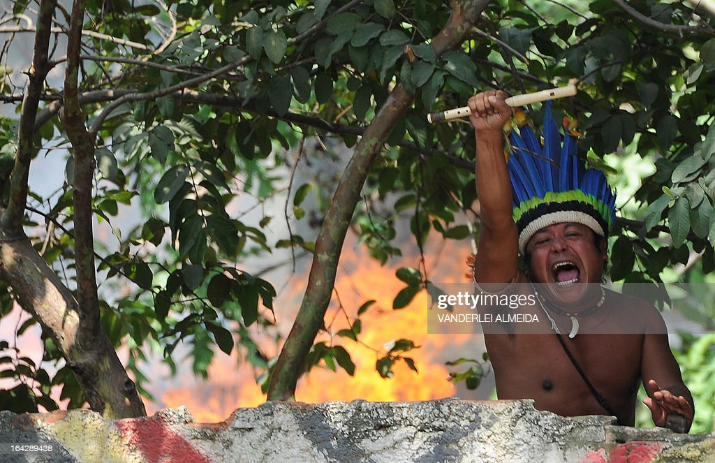 A native gestures as he protests against their eviction from the former Indigenous Museum --aka Aldea Maracana-- next to the Maracana stadium in Rio de Janeiro, Brazil on March 22, 2013. Indigenous people have been occupying the place since 2006, which is due to be pulled down to construct a parking lot for the upcoming Brazil 2014 FIFA World Cup. AFP PHOTO/VANDERLEI ALMEIDA