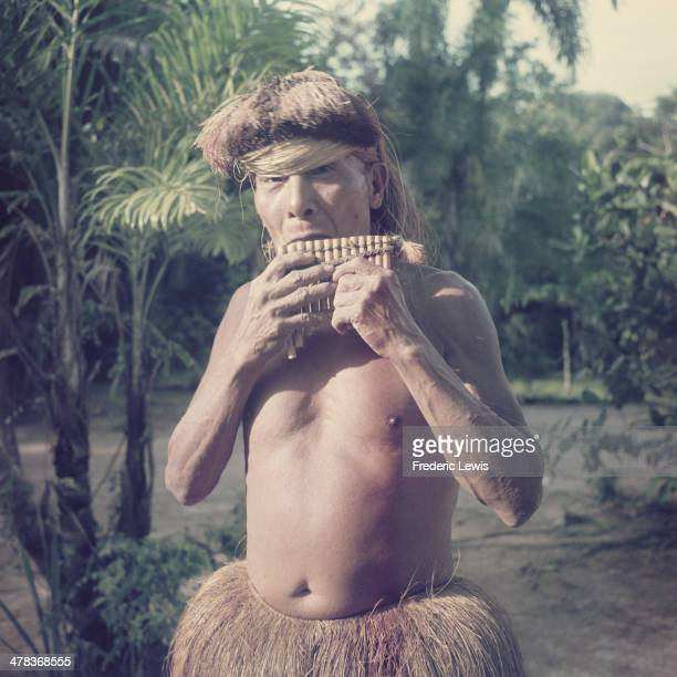 A native man playing the panpipes in the Amazon basin Brazil circa 1960
