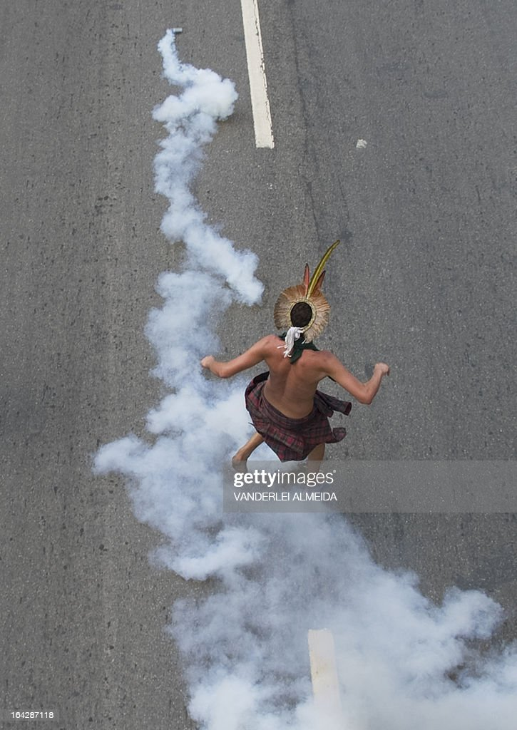 A native returns a tear gas cas launched by riot police as he protests against their eviction outside the former Indigenous Museum --aka Aldea Maracana-- next to the Maracana stadium in Rio de Janeiro, Brazil on March 22, 2013. Indigenous people have been occupying the place since 2006, which is due to be pulled down to construct a parking lot for the upcoming Brazil 2014 FIFA World Cup.