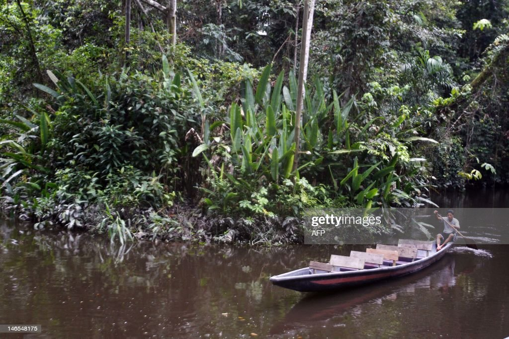 A native sails a canoe at the Sani River, into the Yasuni Ecuadorean National Park, in the Orellana Province,Ecuador, on June 15, 2012. The Yasuni National Park contains Ecuador's largest oil reserves, but its exploitation would imply impacts to pristine ecosystems, particularly watersheds. In 2007, the government of Rafael Correa offered the proposal of not allowing extraction of the Ishpingo-Tambococha-Tiputini (ITT) oil fields in Yasuni, if the world community compensates to leave the oil permanently in the ground.Ecuador will propose at the Rio+20 summit the environmental project, launched in 2010 to prevent the extraction of 846 million barrels of crude oil from the Amazonian Yasuni rainforest, after the country obtained a contribution from international donors of 116,9 million US dollars this first year. AFP PHOTO/Pablo COZZAGLIO