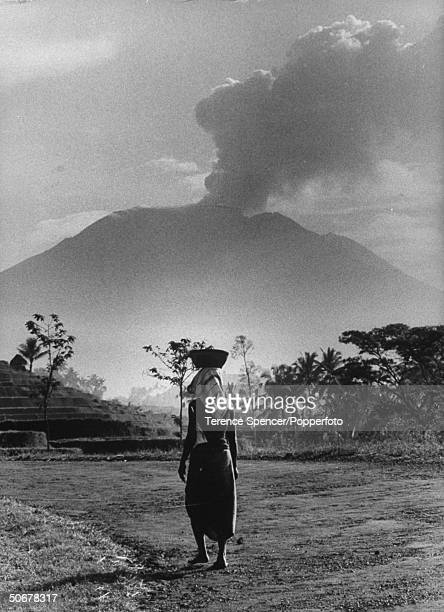 Native woman carrying on tasks with smoking Mt Agung volcano in bkgrd
