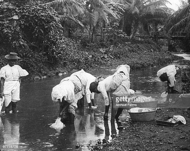 Native women washing clothes in a stream Jamaica