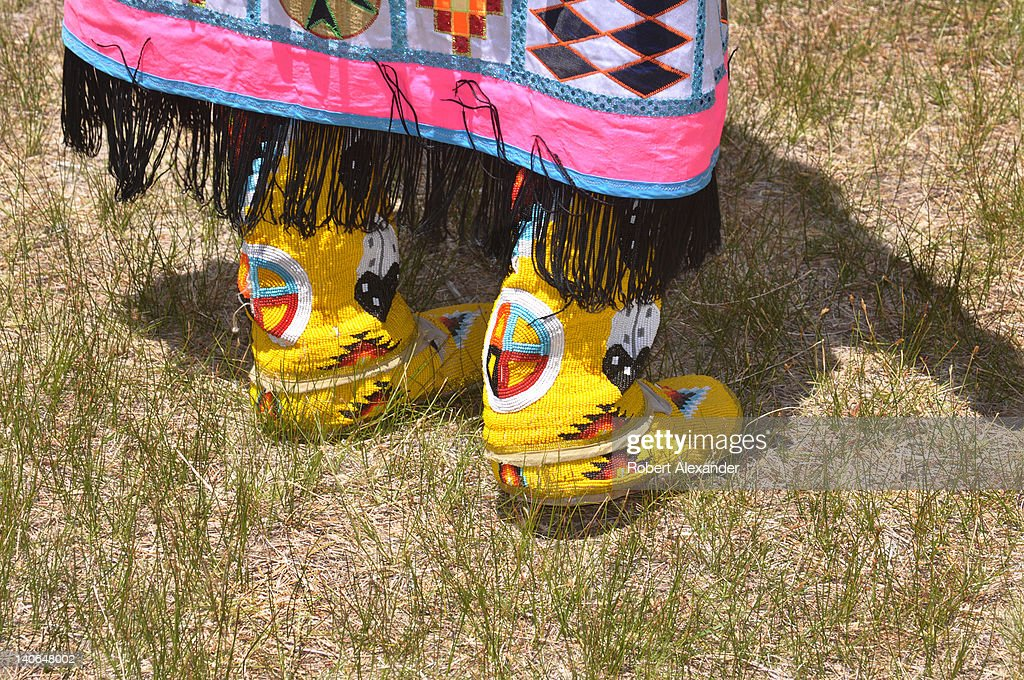 NativeAmerican dancer wearing traditional beaded moccasins waits her turn to compete in competitions at the Taos Pow Wow in Taos Pueblo New Mexico...