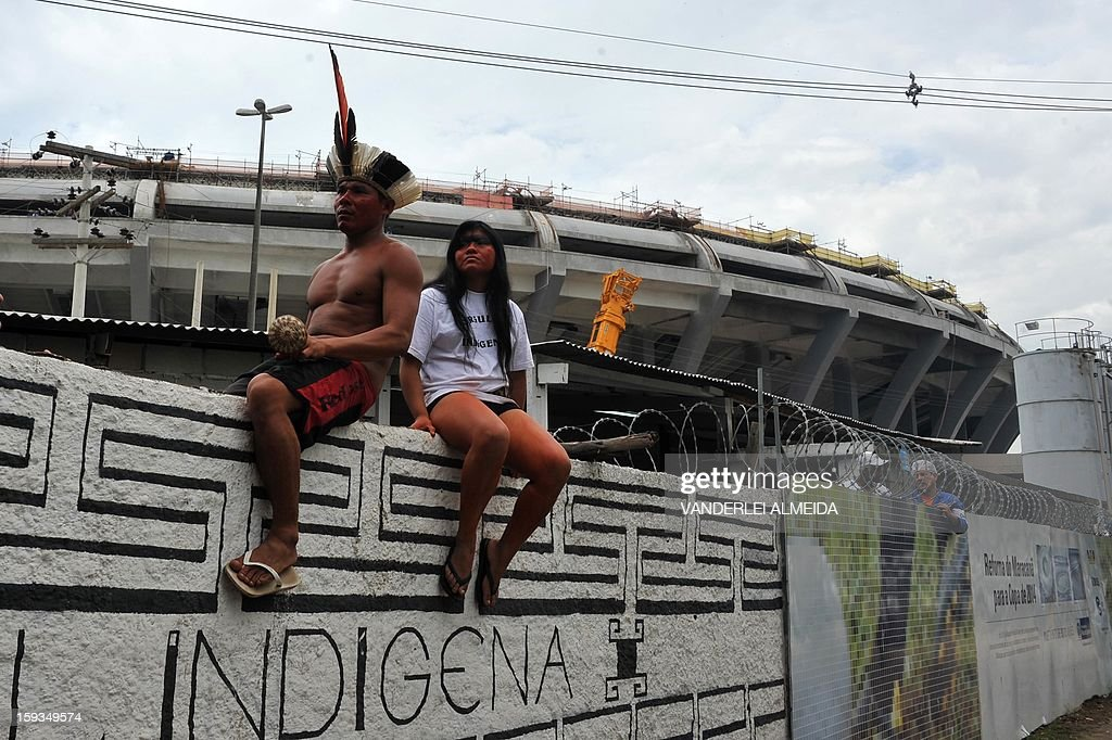 Natives sit on wall looking at riot police officers stand guard at the entrance of the old indigenous museum --aka Aldea Maracana-- next to Maracana stadium in Rio de Janeiro on January 12, 2013. Indians have been occupying the place since 2006 as a protest against Rio de Janeiro's governmet decision to throw them out and pull down the building to construct 10,500 parking lots for the upcoming Brazil 2014 FIFA World Cup. AFP PHOTO/VANDERLEI ALMEIDA