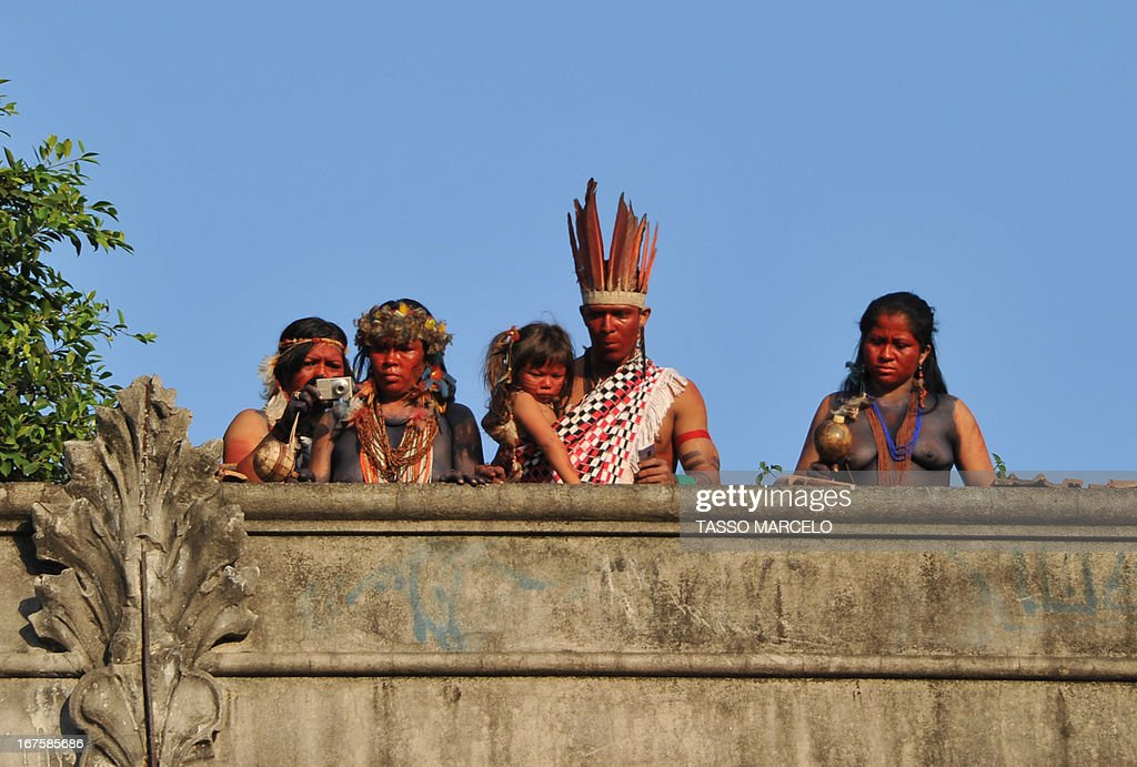 Natives who occupied Rio de Janeiro's former Indian Museum after being evicted more than a month ago, watch on April 26, 2013 from the roof of the building as the shock police battalion clashes with demonstrators opposed to the privatization and demolition of the edifice. On March 22 the police forcibly ejected some 30 indigenous activists and supporters from the Indian Museum located next to the Maracana stadium, the venue for the 2014 World Cup final. The planned demolition is at the center of a months-long legal tussle, with authorities saying they will raze the abandoned colonial-style building at the request of football's world governing body as part of an urban renewal program.