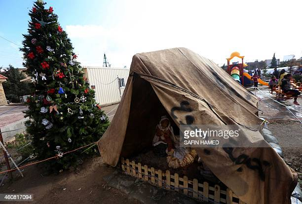 A Nativity scene and chrsitmas tree are seen in the grounds of the Mar Elias Chaldean Catholic Church where Iraqi Christians who fled the violence in...