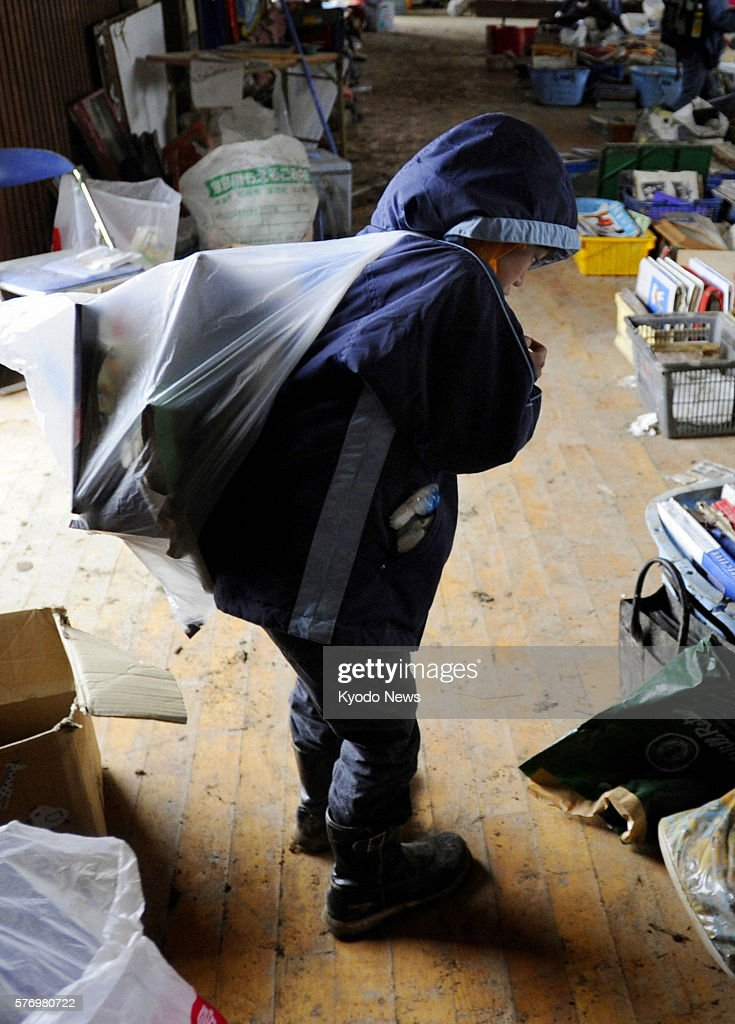 Natori Japan A boy carries a bag of family photos and other sentimental items found at Yuriage Elementary School where items retrieved from debris in...