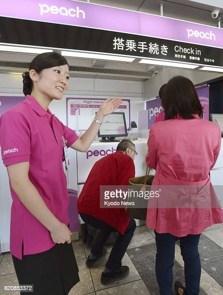 Natori Japan A ground worker guides checkin for a flight of Peach Aviation Ltd at Sendai Airport on April 12 2013 The Japanese lowcost carrier...