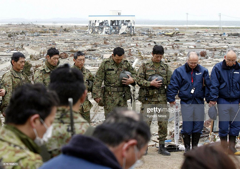 Natori Japan Members of the SelfDefense Forces and firefighters offer silent prayers in Natori Miyagi Prefecture at 246 pm on April 11 the exact...