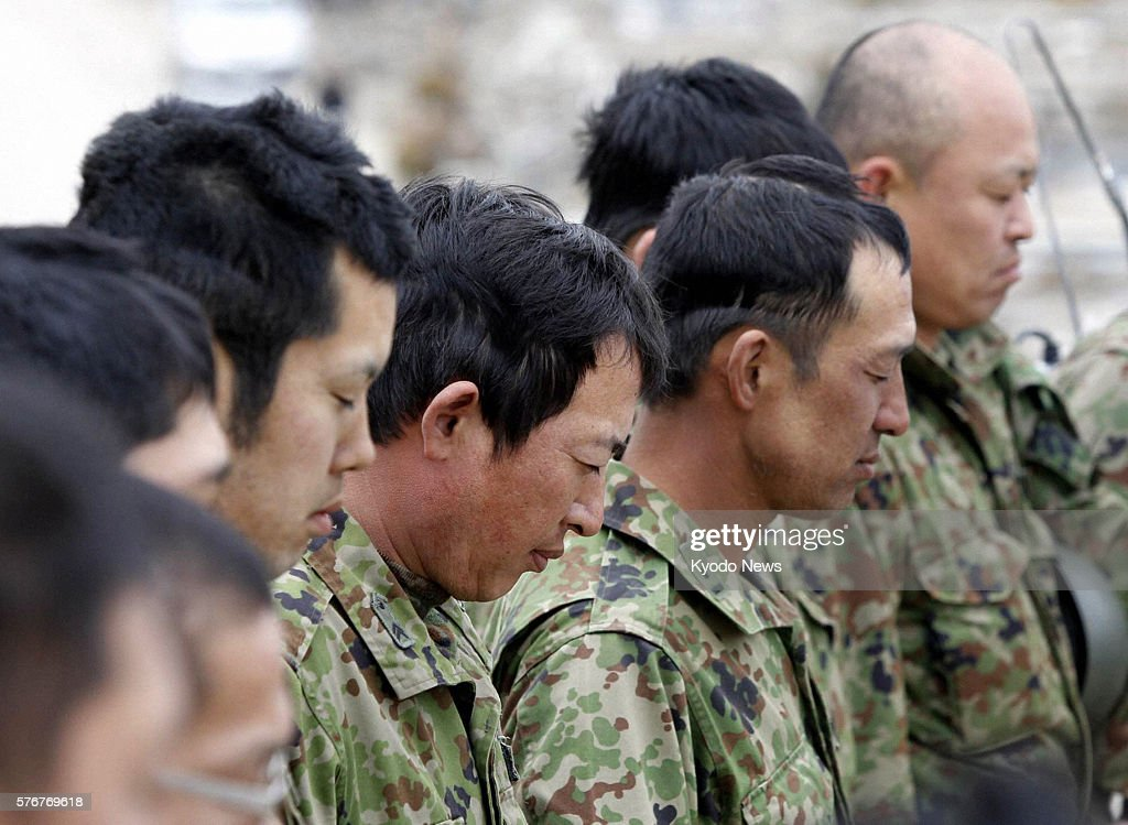 Natori Japan Members of the SelfDefense Forces offer silent prayers in Natori Miyagi Prefecture at 246 pm on April 11 the exact moment the historic...
