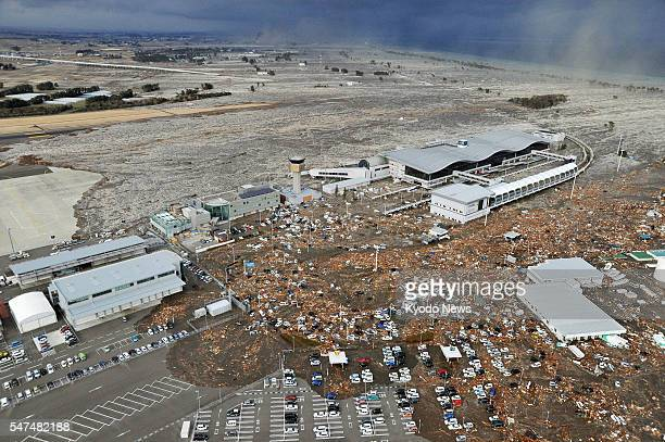 Natori Japan Sendai airport in Miyagi Prefecture northeastern Japan is seen swamped by a tsunami after a powerful quake in a photo taken from a Kyodo...