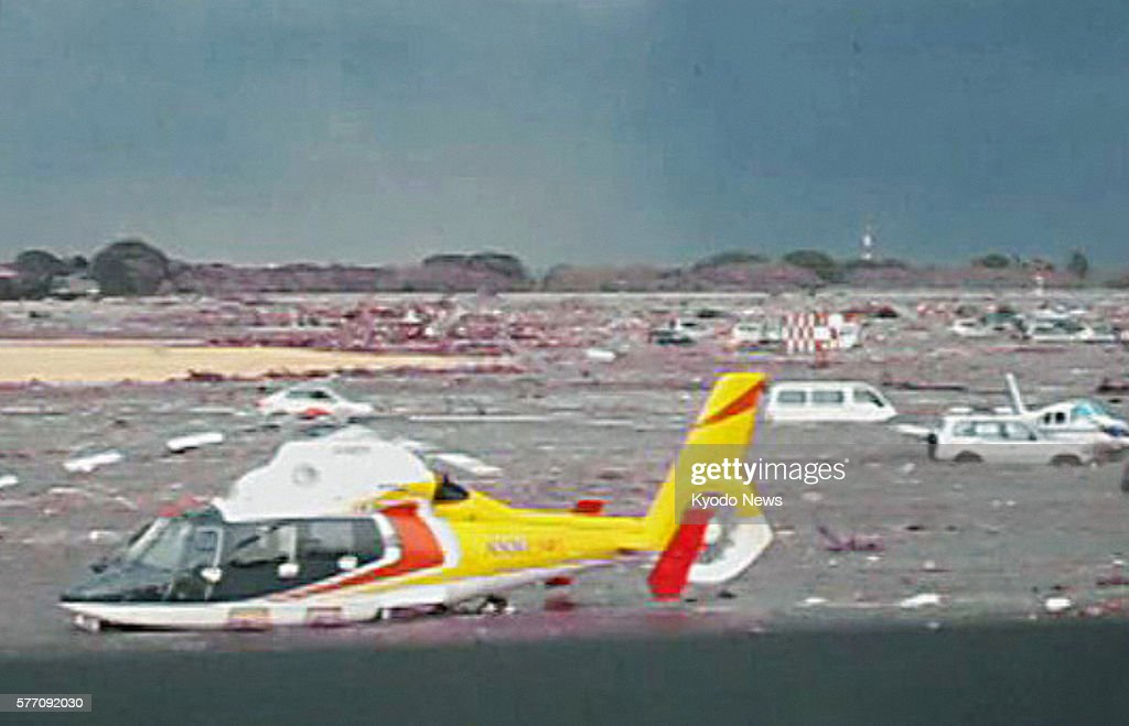 Natori Japan Still image taken from video footage shows a helicopter and cars being swept away by a tsunami at Sendai airport in Miyagi Prefecture at...