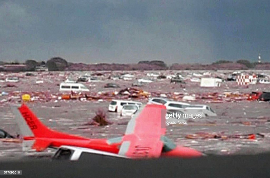 Natori Japan Still image taken from video footage shows a light airplane and cars being swept away by a tsunami at Sendai airport in Miyagi...
