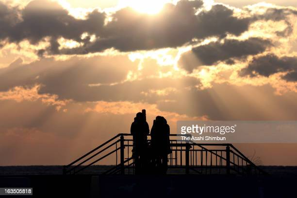 Natsuki Takatsuna and his father Hiroyuki pray toward the sea to commemorate the victims on March 11 2013 in Iwaki Fukushima Japan Japan marks second...