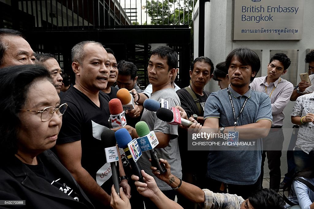 Natthawut Saikua (2nd L), a leader of Thailand's pro-democracy 'Red Shirt' street movement, answers reporters' questions outside the British Embassy in Bangkok on June 27, 2016. Activists on June 27 urged Britain to hand over details of the multi-million-dollar sale to Thailand of fake bomb detectors that led to the detention of scores of innocent people. British fraudster Gary Bolton was jailed in 2013 for making millions selling the GT200 -- which he billed as a 'magic wand' able to detect tiny particles of explosives or drugs from hundreds of metres away. / AFP / CHRISTOPHE