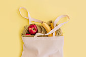 Natural eco bag with fruits on yellow background. Zero waste shopping and plastic free concept. Eco friendly, flat lay.