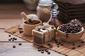 Natural handmade soap, aromatic cosmetic oil, sea salt with coffee beans on rustic wooden background. Healthy skin care. Sauna and SPA concept.