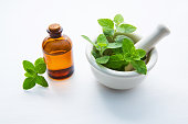 Natural Mint Essential Oil in a Glass Bottle with Fresh Mint Leaves in white porcelain mortar.