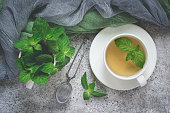 Natural mint tea and fresh mint leaves on a gray background.