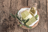 natural olive oil soap bars and olive oil bottle in a basket on wooden table