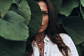 Close-up of young woman looking at camera while standing among the leaves outdoors