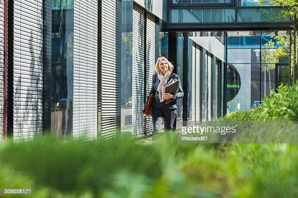 Nature businesswoman carrying briefcase and files
