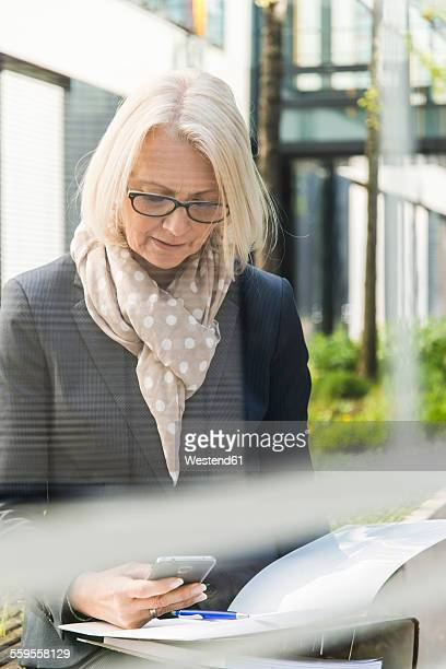 Nature businesswoman with files using mobile phone