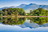 Summer woodland reflected in a perfectly still Derwent Water with dramatic Latrigg mountain backdrop in the beautiful English Lake District. ProPhoto profile for precise color reproduction.