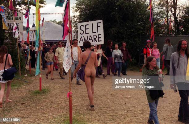 A naturist with a placard reading 'Self Aware' strolls amongst other festival goers at the Glastonbury Music Festival 2000 in Pilton Somerset