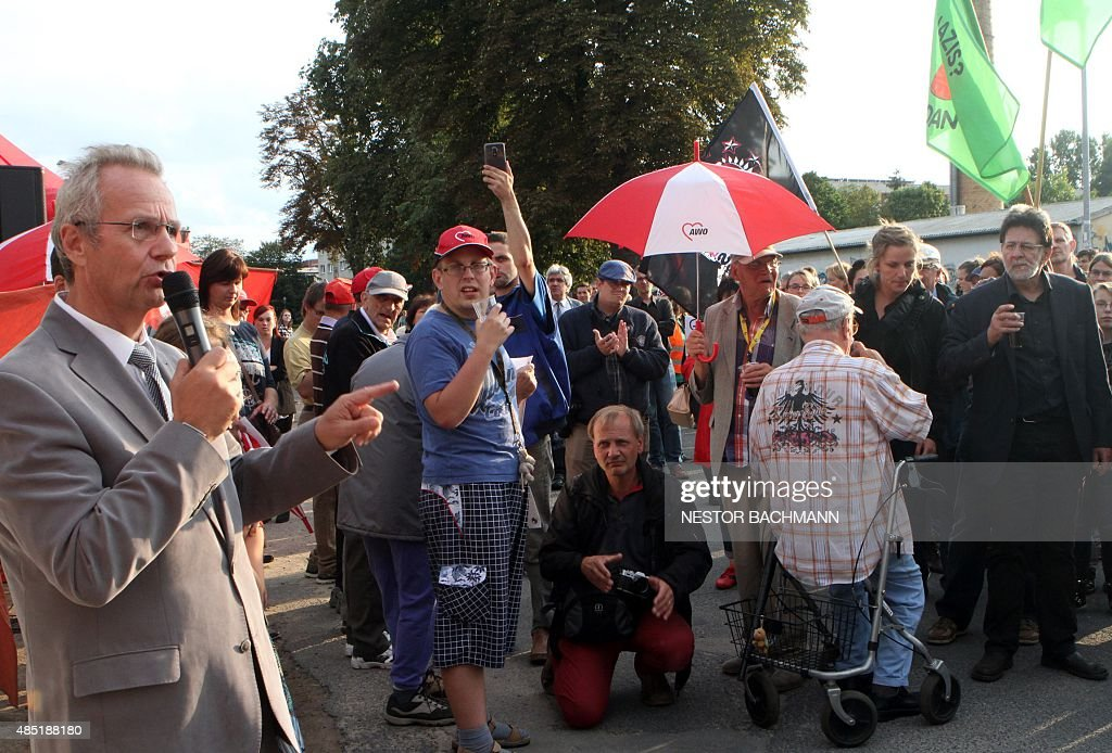 Nauen Mayor Detlef Fleischmann speaks to people protesting against the suspected arson attact on a sports hall meant to house refugees from September...
