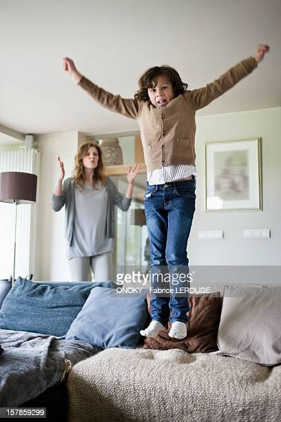 Naughty boy jumping on couch with his mother scolding him