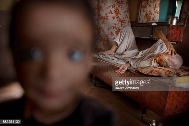 A naughty child with his grandmother a very old widow lying on her bed in her family's house on October 13 2005 at Varanasi Uttar Pradesh India Many...