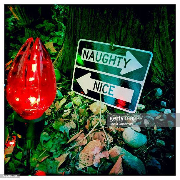 Naughty Nice Sign Leaning On Tree Lit Up With Red Christmas Light