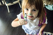 Little child holds up a marker, she has drawn all over her face
