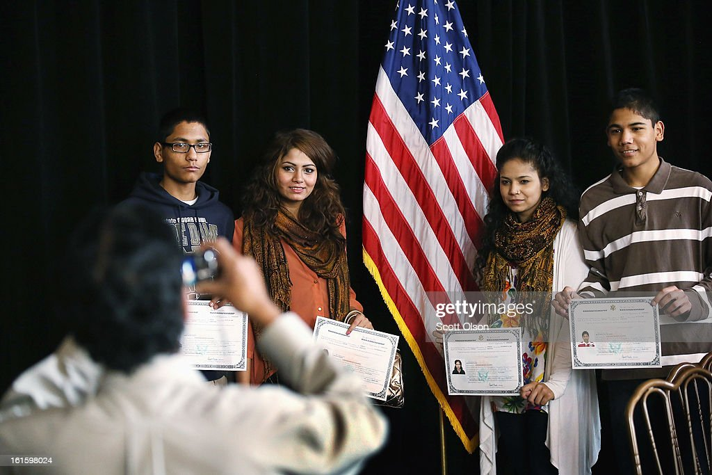Naushad Hussain, from Pakistan, takes pictures of his children, (L toR) Fourteen-year-old Own,18-year-old Rabia (L) and 16-year-old Kulsoom, and Own's twin brother Mohammad, after they received citizenship certificates during a ceremony at the Chicago Cultural Center on February 12, 2013 in Chicago, Illinois. The ceremony was held to recognize as new U.S. citizens 62 children, ages 6-18, from 23 countries who were adopted from abroad or who derived U.S. citizenship when their immigrant parents were naturalized.