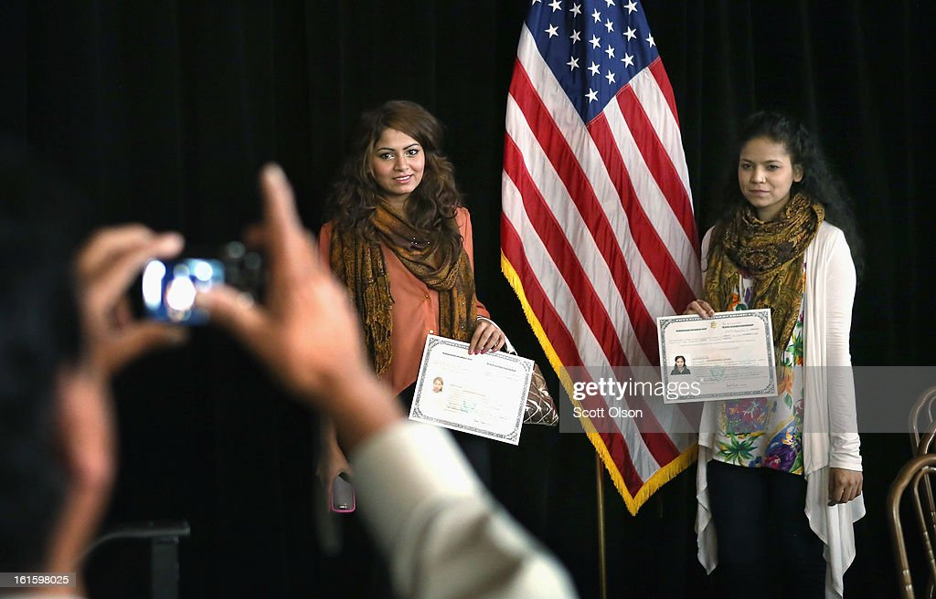 Naushad Hussain, from Pakistan, takes pictures of his daughters, 18-year-old Rabia (L) and 16-year-old Kulsoom, after they received citizenship certificates during a ceremony at the Chicago Cultural Center on February 12, 2013 in Chicago, Illinois. The ceremony was held to recognize as new U.S. citizens 62 children, ages 6-18, from 23 countries who were adopted from abroad or who derived U.S. citizenship when their immigrant parents were naturalized.