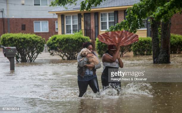 Nautical Jackson left and Aniya Ruffin walk through floodwaters with their dog Chestnut as water threatens to enter their home on Dacian Road in...