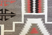 Authentic historic Navajo woven wool blanket design showing age and use stains.  The Navajo stained their yarns for fabrics using natural items from the surroundings - beige from corn silk, tan from b