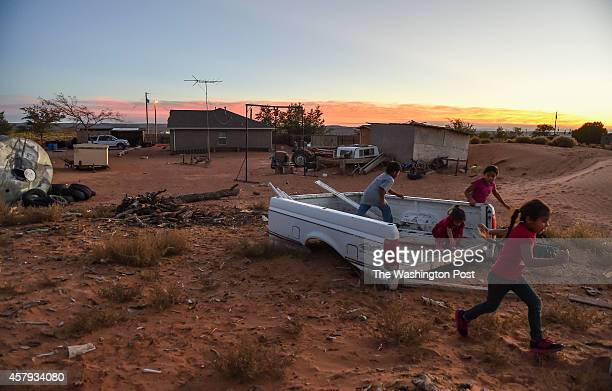Navajo Indian children Arlen Begay left Amanda Begay center Ileana Angeles rear and Karleah Angeles foreground right play on a pickup truck's bed on...