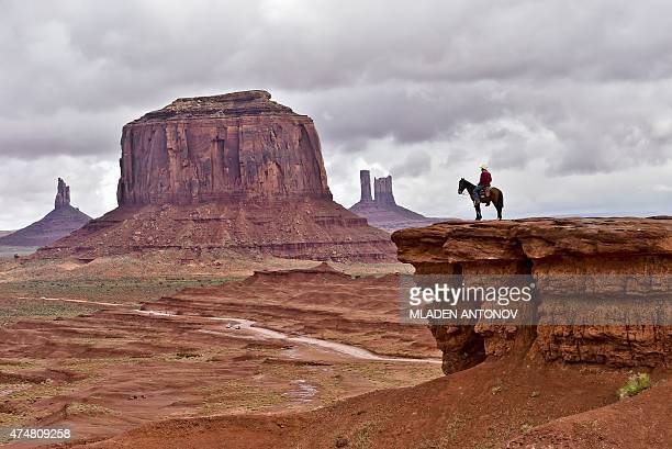 A Navajo man on a horse poses for tourists in front of the Merrick Butte in Monument Valley Navajo Tribal Park Utah on May 16 2015 AFP PHOTO / MLADEN...