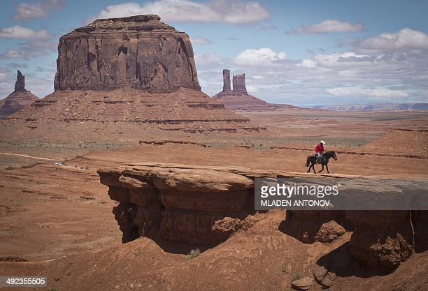 A Navajo man on a horse rides away after posing for tourists in front of the Merrick Butte in Monument Valley Navajo Tribal park Utah on May 12 2014...
