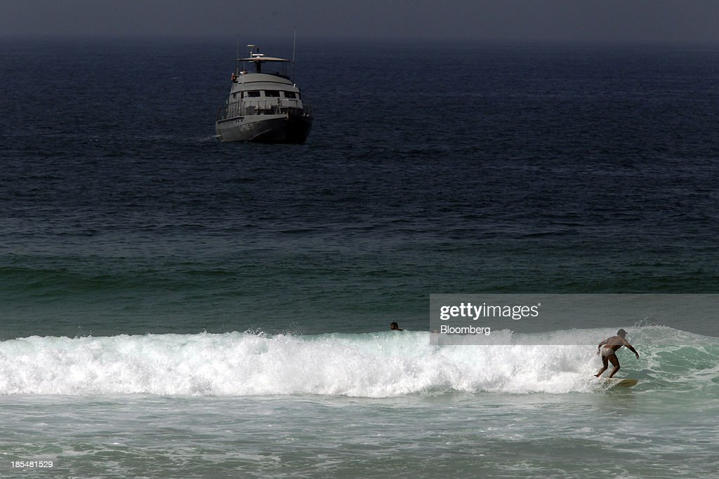 A naval boat patrols off the coast near the Windsor Barra Hotel while a man surfs in Rio de Janeiro, Brazil, on Monday, Oct. 21, 2013. Soldiers, army vehicles, helicopters and navy ships are guarding a Rio de Janeiro hotel where companies including China National Petroleum Corp., Royal Dutch Shell Plc and Total SA are expected to vie for one of the worlds two largest offshore fields at 3 p.m. local time, as oil workers protest the Dado Galdieri/Bloomberg via Getty Images