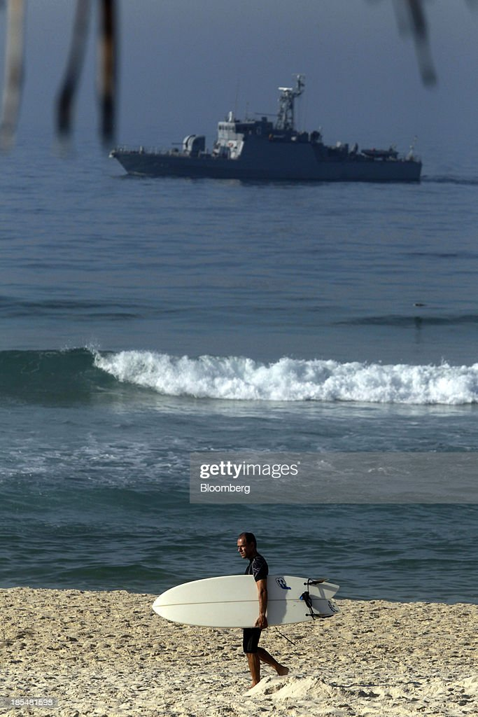 A naval boat patrols off the coast near the Windsor Barra Hotel while a man carries a surf board on the beach in Rio de Janeiro, Brazil, on Monday, Oct. 21, 2013. Soldiers, army vehicles, helicopters and navy ships are guarding a Rio de Janeiro hotel where companies including China National Petroleum Corp., Royal Dutch Shell Plc and Total SA are expected to vie for one of the worlds two largest offshore fields at 3 p.m. local time, as oil workers protest the concession. Photographer: Dado Galdieri/Bloomberg via Getty Images