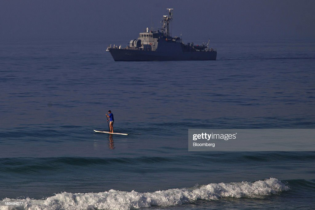A naval boat patrols off the coast near the Windsor Barra Hotel while a man paddleboards in Rio de Janeiro, Brazil, on Monday, Oct. 21, 2013. Soldiers, army vehicles, helicopters and navy ships are guarding a Rio de Janeiro hotel where companies including China National Petroleum Corp., Royal Dutch Shell Plc and Total SA are expected to vie for one of the worlds two largest offshore fields at 3 p.m. local time, as oil workers protest the concession. Photographer: Dado Galdieri/Bloomberg via Getty Images