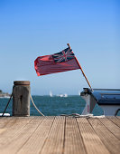 Naval Civil Ensign flag fluttering in the strong breeze on small boat moored up on a jetty at Brownsea Island, Poole, Dorset, UK