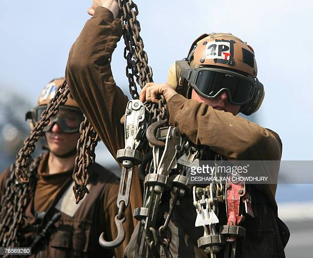 A US naval crewmember holds the tow chains on the US supercarrier USS Kitty Hawk in the Bay of Bengal during the Malabar exercise 07 September 2007...