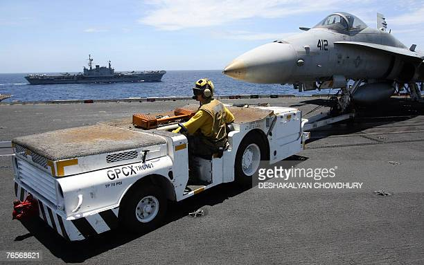A US naval crewmember tows a fighter craft as India's lone aircraft carrier the INS Viraat sails alongside the US supercarrier USS Kitty Hawk in the...